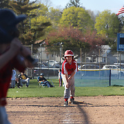 A young baseball player waits at third base as the batter prepares for a pitch during the Norwalk Little League baseball competition at Broad River Fields,  Norwalk, Connecticut. USA. Photo Tim Clayton