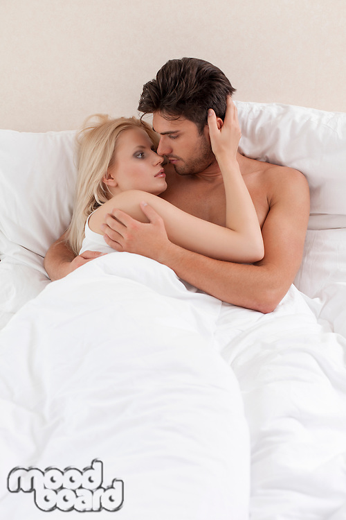 Young couple cuddling in bed