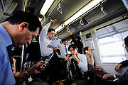 """Commuters use mobile phones and prsonal gaming devices on a train in Tokyo, Japan. The Japanese are well known for their civility and politeness,  but a recent governmental campaign to clamp down on lewd behavior that may inconvenience others -- including talking on cell phones and applying makeup while commuting on a train -- was fueled by a decline in everyday etiquette and manners. The series of posters has a headline that reads """"Please do it at home."""""""