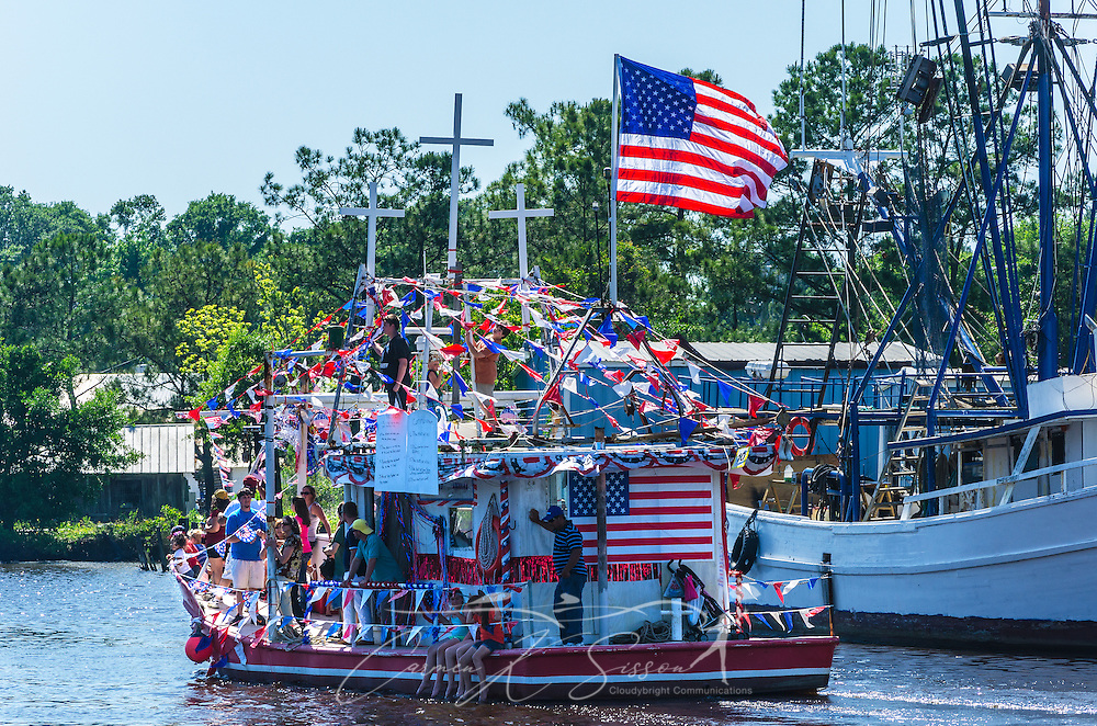 """Why Bother"" participates in the 65th annual Blessing of the Fleet in Bayou La Batre, Alabama, May 4, 2014. The vessel took third place among the decorated, large commercial boats. The first fleet blessing was held by St. Margaret's Catholic Church in 1949, carrying on a long European tradition of asking God's favor for a bountiful seafood harvest and protection from the perils of the sea. The highlight of the event is a blessing of the boats by the local Catholic archbishop and the tossing of a ceremonial wreath in memory of those who have lost their lives at sea. The event also includes a land parade and a parade of decorated boats that slowly cruise through the bayou. (Photo by Carmen K. Sisson/Cloudybright)"