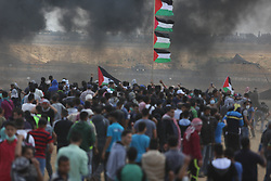Palestinian protesters take part during clashes with Israeli soldiers at the border fence with Israel east of Khan Yunis in the southern Gaza Strip, Israeli soldiers killed at least 60 Palestinians and wounded more than 2,700. as demonstrations on the Gaza-Israel border coincided with the controversial opening of the U.S. Embassy in Jerusalem. This marks the deadliest day of violence in Gaza since 2014. Gaza's Hamas rulers have vowed that the marches will continue until the decade-old Israeli blockade of the territory is lifted. Gaza Strip, Palestine, May 15, 2018. Photo by Ashraf Amra/SalamPix/ABACAPRESS.COM
