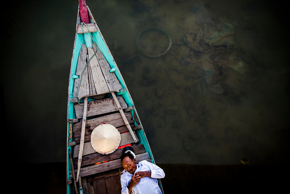A fisherman takes a nap on his boat, beneath a bridge in the Old Town of Hoi An in central Vietnam.