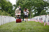 A family walks through graves as they pay a visit during Memorial Day observances at Arlington National Cemetery.