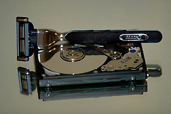 Mirrored imaged of a Gillette Mach 3 razor on an opened computer hard drive.