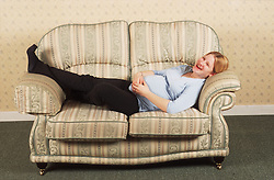 Pregnant teenage girl lying on sofa laughing,