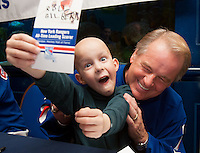 A young cancer patient at New York City's Ronald McDonald House helps New York Rangers hockey legend Rod Gilbert sign autographs.