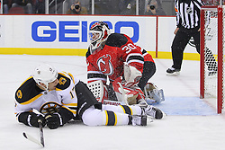 Jan 4, 2012; Newark, NJ, USA; Boston Bruins left wing Milan Lucic (17) lies in front of New Jersey Devils goalie Martin Brodeur (30) after a save during the first period at the Prudential Center.