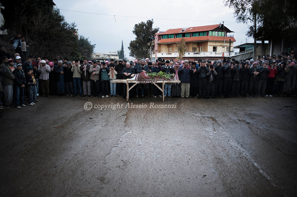 SYRIA - Al Qsair. Mourners at the funeral of Asem Bader Waw, 31 y.o., shot dead by a Syrian Army's sniper on January 31, 2012. Al Qsair is a small town of 40000 inhabitants, located 25Km south-west of Homs. The town is besieged since the beginning of November and so far it counts 65 dead. ALESSIO ROMENZI