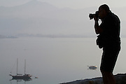 Silhouette of a photographer photographing sailing boats in the early morning light.