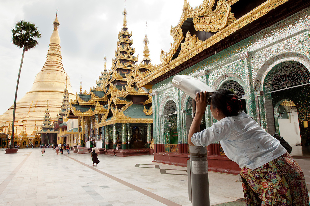 Burmese women zooms in on the peak of the Shwedagon Pagoda in Yangon, Myanmar. Shwedagon Pagoda is the most sacred Buddhist pagoda for the Burmese with relics of the past four Buddhas enshrined within.