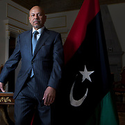Ali Suleiman Aujali, the former Libyan Ambassador to the US, who quit his post as Ambassador when he broke with Colonel Muammar el-Qaddafi in late February, has set up an office at the ambassador's residence representing the Libyan opposition. He stands next to the flag of The National Transitional Council of the Libyan Republic. This flag previously represented Libya between 1951 and 1969 was initially used by protestors during the 2011 Libyan uprising and is being flown at Libyan diplomatic missions supporting the National Transitional Council.