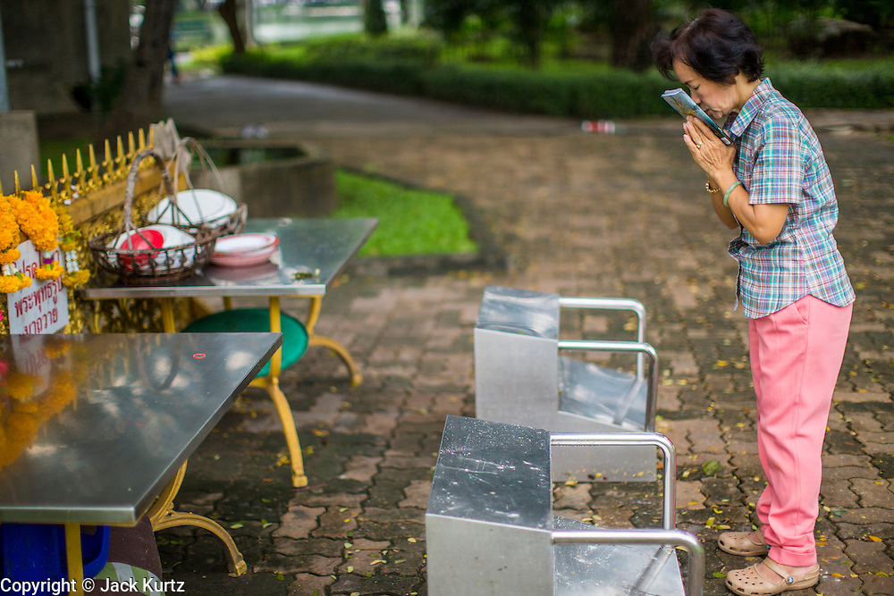 06 OCTOBER 2012 - BANGKOK, THAILAND:  A woman prays at a shrine in Lumphini Park in Bangkok. The Thai government promotes exercise classes as a way staying healthy. Lumphini Park is 142 acre (57.6-hectare) park in Bangkok, Thailand. This park offers rare open public space, trees and playgrounds in the congested Thai capital. It contains an artificial lake where visitors can rent boats. Exercise classes and exercise clubs meet in the park for early morning workouts and paths around the park totalling approximately 1.55 miles (2.5 km) in length are a popular area for joggers. Cycling is only permitted during the day between the times of 5am to 3pm. Smoking is banned throughout smoking ban the park. The park was created in the 1920's and named after Lumbini, the birthplace of the Buddha in Nepal.   PHOTO BY JACK KURTZ