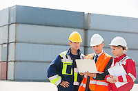 Workers discussing over laptop in shipping yard