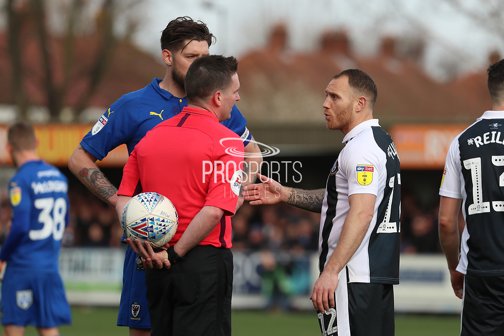 Gillingham defender Barry Fuller (12) and AFC Wimbledon midfielder Anthony Wordsworth (40) talking to the ref during the EFL Sky Bet League 1 match between AFC Wimbledon and Gillingham at the Cherry Red Records Stadium, Kingston, England on 23 March 2019.