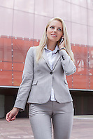 Beautiful young businesswoman conversing on cell phone while standing against office building