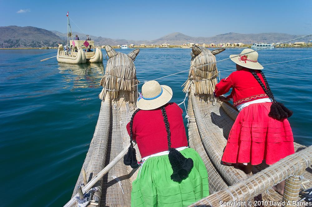 Women rowing reed boat, Uros Island, Puno, Peru