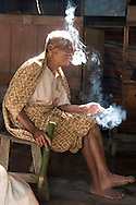 Rantepao, Tana Toraja, Sulawesi, Indonesia, October 2010. A man drinks rice wine and smokes tobacco at the tabacco bar.  Market day in Rantepao.  The Toraja people live a traditional life in the forested mountains of South Sulawesi.  Photo by Frits Meyst/Adventure4ever.com