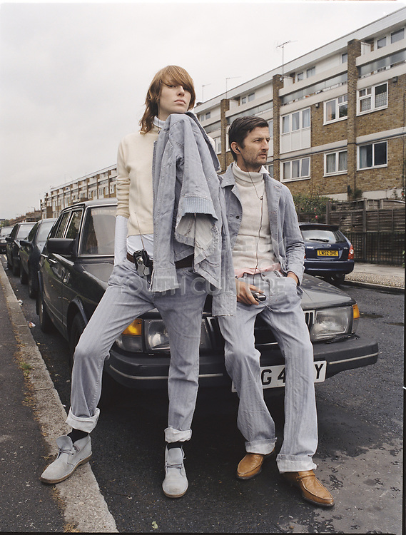 Man and woman wearing matching outfits posing by car bonnet.