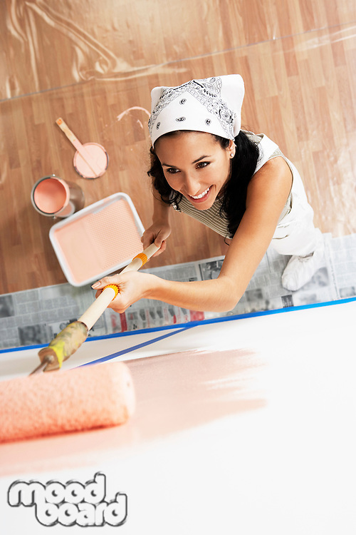 Woman painting interior wall with roller elevated view
