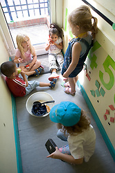 Group of children at Nursery School sitting in the corridor,
