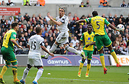 Chico Flores of Swansea City (c) heads the ball past Norwich City Captain Sebastien Bassong.<br /> Barclays premier league match , Swansea city v Norwich city at the Liberty stadium in Swansea, South Wales on Saturday 29th March 2014.<br /> pic by Phil Rees, Andrew Orchard sports photography.