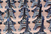 Mini Eiffel Towers are for sale everywhere in Paris, carefully laid out in rows for display.