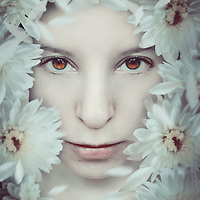 portrait of a young girl's face surrounded by white flowers