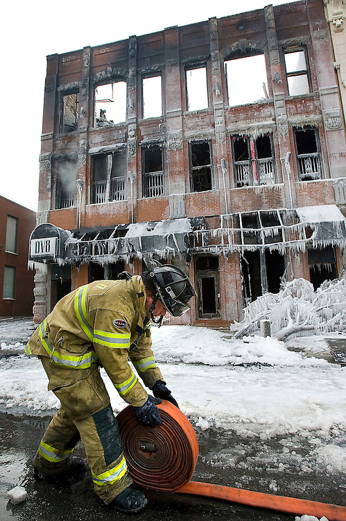 Salt Lake City fireman Eric Myers rolls up a fire hose to put them away after Fire crews worked to put out the remnants of a fire that burned the DV8 building as crews from McKay Demolition prepareto demolish it in Salt Lake City, Utah Thursday, Jan.24, 2008. August Miller/ Deseret Morning News .