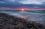 A glowing sunset kisses the waves and rocks along the Lake Superior shore.  <br />