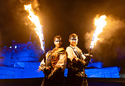 Fire artists taking part in Hogmanay Torchlight Procession perform at Edinburgh Castle prior to procession along the  Royal Mile in the Old Town , Scotland, UK