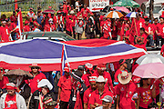 Mar. 28, 2010 - BANGKOK, THAILAND: Red Shirt protestors carry the Thai flag through Bangkok streets near the 11th Infantry Regiment barracks in Bangkok Sunday. More than 10,000 anti government Red Shirt protestor picketed the entrance to the Royal Thai Army's 11th Infantry Regiment Sunday in a continuation of protests that started March 21. The Red Shirts won a key victory Sunday when Thai Prime Minister Abhisit Vejjajiva agreed to negotiate with the protest leaders. The Red Shirts support former Prime Minister Thaksin Shinawatra, who was deposed in a coup in 2006 and went into exile rather than go to prison after being convicted on corruption charges. Thaksin is still enormously popular in rural Thailand. PHOTO BY JACK KURTZ
