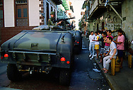 A convoy of humvees with US soldiers drive through downtown Panama City to secure a neighborhood from Panamanian army troops during the US invasion, December 1989.