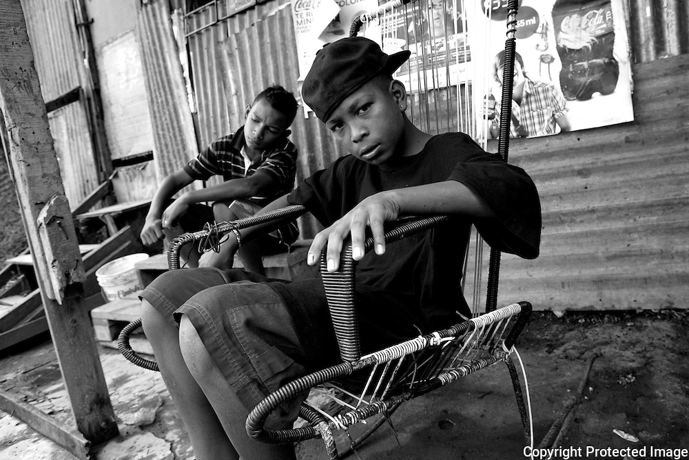 Chara (Kevin) sits in a rocking chair outside a corner store in Los Pinos with his friend Dianko. Both boys have been getting into trouble. Dianko has been sniffing glue and getting into fights. Chara had been making guns at home to use to assault girls, had dropped out of school and got high with Dianko for the first time a few days ago.