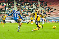 Will Grigg of Wigan Athletic gets a shot in ahead of Zak Whitbread of Shrewsbury Town during the Sky Bet League 1 match at the DW Stadium, Wigan<br /> Picture by Matt Wilkinson/Focus Images Ltd 07814 960751<br /> 21/11/2015