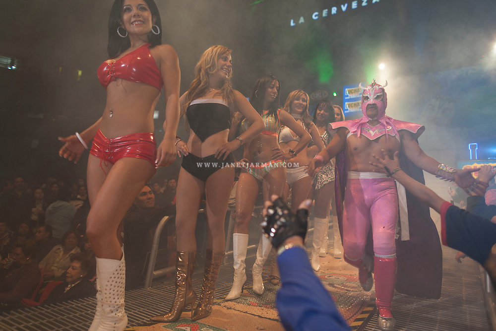 """Fans reach out to touch a """"luchador""""  during his grand entrance to compete in a Friday night event held at Arena Mexico, Mexico City's largest Lucha Libre venue, which holds nearly 17,000 spectators."""