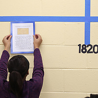 Josalyn Johnson, 13, hangs the first poster outlining the beginning of the State of Mississippi as part of a timeline of the states history as part of next week's Bicentennial celebration.