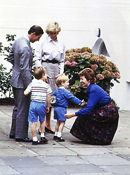 "File photo dated 16/09/87 of the three-year-old Duke of Sussex (front centre), then Prince Harry, shaking the hand of headmistress Jane Mynors as he arrives for his first day of nursery school with his parents, the Prince and Princess of Wales, and his brother Prince William, at Chepstow Villas in west London with a Thomas the Tank Engine bag. The Duke of Sussex has recorded an on-camera introduction to the new animated special ""Thomas & Friends: The Royal Engine""."