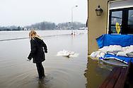 Nederland, Deventer, 14 jan 2011.Hoog water in de IJssel. In Deventer zijn zandzakken neergelegd om de huizen aan de ijsselkade te beschermen tegen het hoge water. Morgen stijgt het waterpeil nog..Een meisje staat op een muurtje dat onder water staat, mensen kijken door het raam. ..Foto (c)  Michiel Wijnbergh