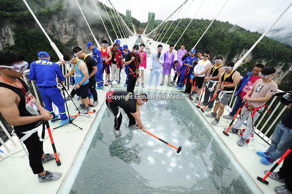 ZHANGJIAJIE, CHINA - JUNE 25:<br /> <br /> A visitor strikes the glass-bottomed bridge with a hammer for a safety test at Zhangjiajie Grand Canyon on June 25, 2016 in Zhangjiajie, Hunan Province of China. World\'s tallest and longest glass-bottomed bridge has been completed and took a global broadcast through television and internet medias to show its safety. More than thirty citizens and visitors thumped the bridge with hammer in the test event. <br /> &copy;Exclusivepix Media