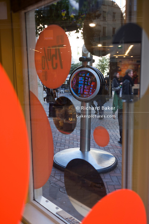Circle shapes for a 75% sale in department store Liberty's window and Carnaby street pedestrians.