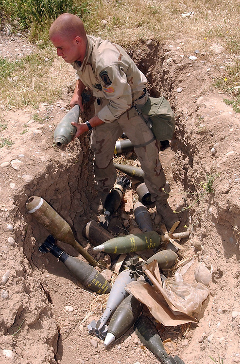 Sgt. Mathew Papke, from Falls Church, VA, with the U.S. Army Engineers from the 173rd Brigade Combat Support Company, from Vicenza, Italy, carefully lifts a 120 mm morter shell out of trench dug into a soccer field in Karkuk, Iraq. The engeinners went out into the northern Iraqi city of Karkuk to recover chaches of Iraqi military weapons and munitions to keep them from falling into the hands of Saddam loyalist and to make the town safer for its residents. Tons of explosive shells were stored at a school and were left strewn around a neighborhood soccer field.(Alan Lessig/Army Times)