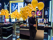"27 MARCH 2015 - BANGKOK, THAILAND: A worker in the Yves St. Laurent store in EmQuartier prepares to greet customers with umbrellas during the grand opening of the new mall. ""EmQuartier"" is across Sukhumvit Rd from Emporium. Both malls have the same corporate owner, The Mall Group, which reportedly spent 20Billion Thai Baht (about $600 million US) on the new mall and renovating the existing Emporium. EmQuartier and Emporium have about 450,000 square meters of retail, several hotels, numerous restaurants, movie theaters and the largest man made waterfall in Southeast Asia. EmQuartier celebrated its grand opening Friday, March 27.    PHOTO BY JACK KURTZ"