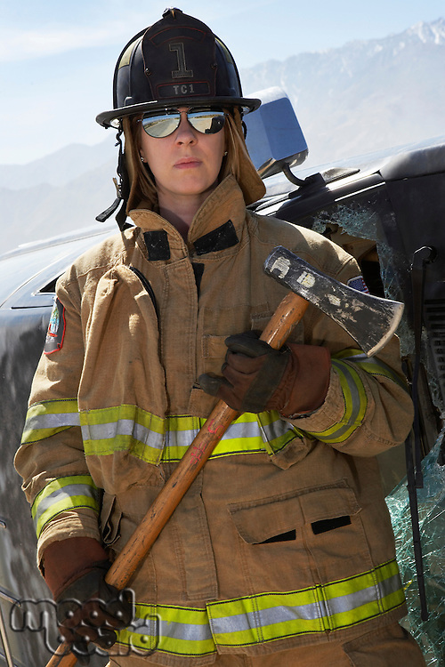 Portrait of female firefighter holding axe
