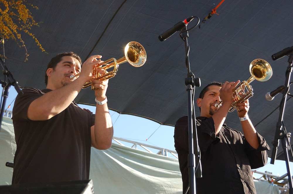 Calexico horn section plays during the headliner concert at Tucson's first-ever Fiesta en el Barrio Viejo in 2010. The all-day concert is now known as Fiesta en el Barrio. Event photography by Martha Retallick.