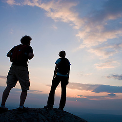 A couple watches the sunset on the summit of Mount Monadnock in Monadnock State Park in Jaffrey, New Hampshire.