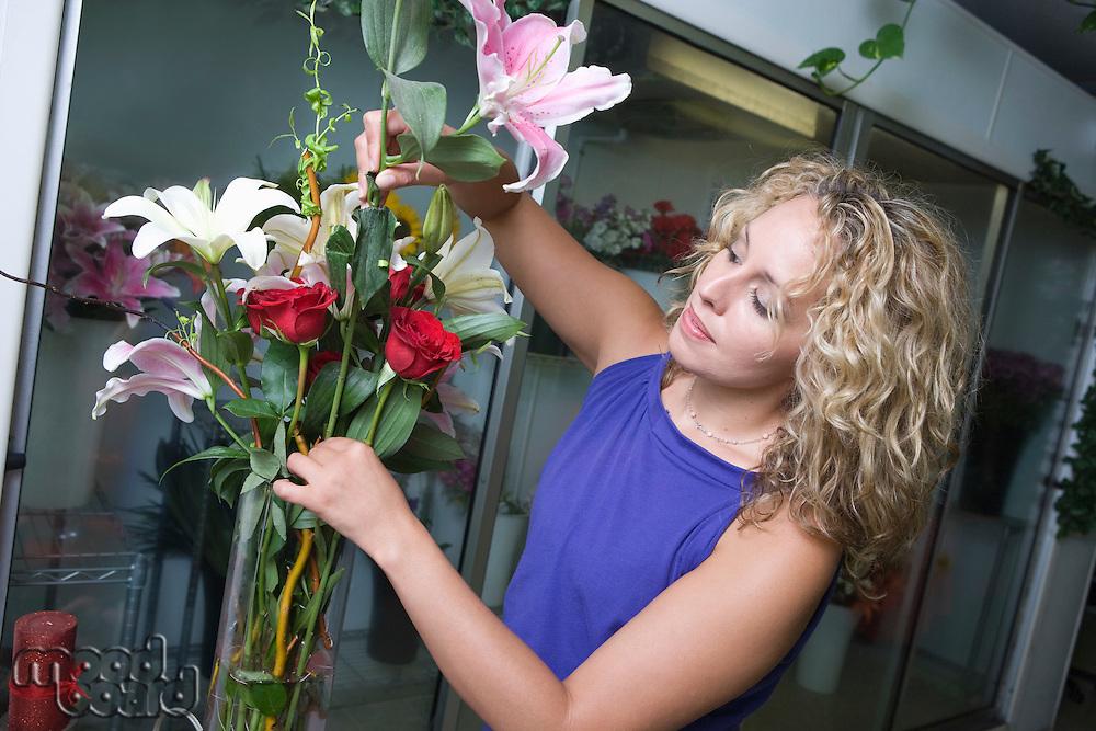Female florist arranging flowers in vase
