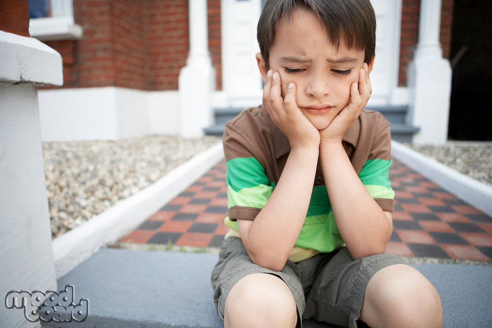 Sad little boy sitting on front steps of house close up