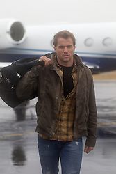 man at a small airport walking by a plane with a bag over his shoulder