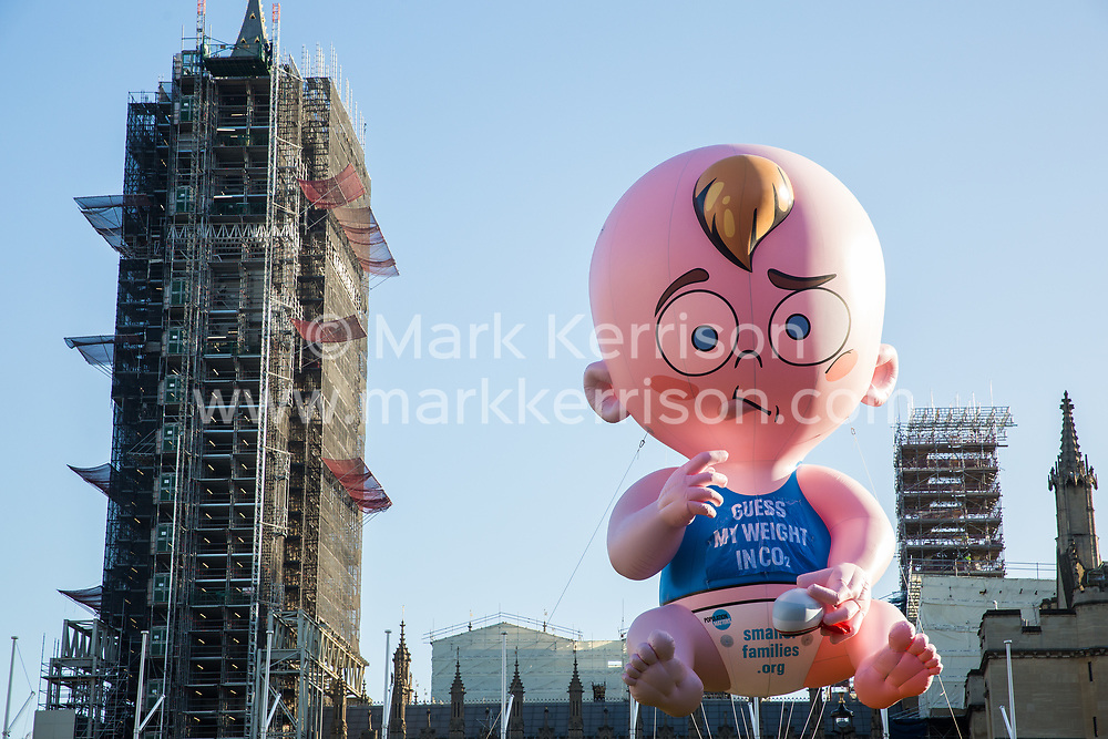 London, UK. 29 November, 2019. A blimp is raised by activists from Population Matters in Parliament Square during the Youth Strike for Climate. Population Matters argues that larger families contribute to the current environmental crisis, resulting in climate change, poverty and species extinction.