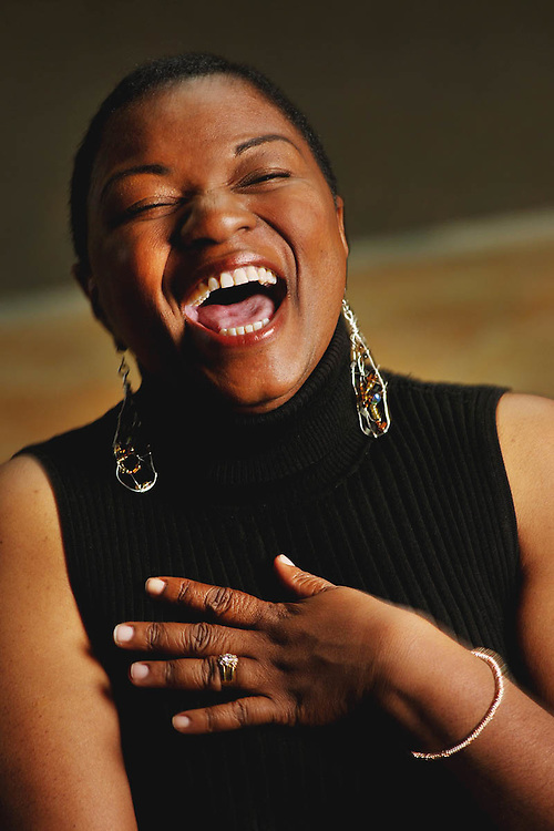 An African-American woman wearing a black, sleeveless turtle neck laughs during her portrait session in Raleigh, NC.